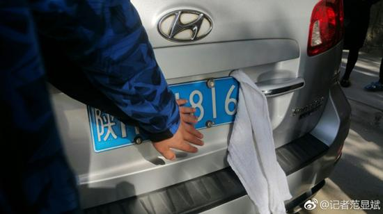 公车司机用毛巾遮掩车牌。