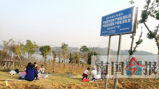 """12月9日,环江滨水大道沿线,在""""严禁烧烤""""的宣传提醒牌下,仍有市民在举行露天烧烤。 广西新闻网-南国今报 图"""