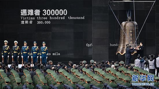 2017年12月13日,南京大屠杀死难者国家公祭仪式在南京举行。图为南京各界代表撞响和平大钟。 新华社 图
