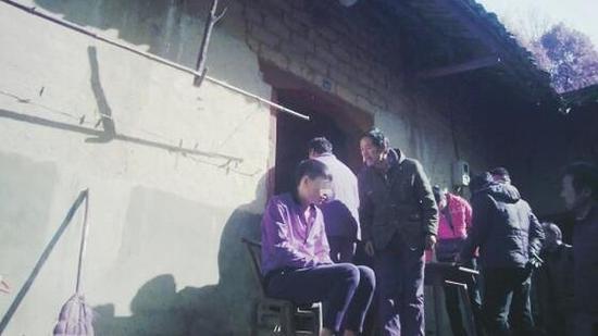 1月10日,长沙莲花镇金华村,第一拨催收人员坐在凳子上,气愤的亲友上前指责。