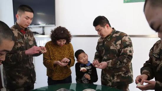军嫂刘铭俊和官兵们一起包饺子。记者孙萌摄
