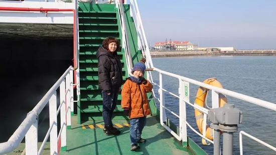 军嫂刘铭俊与儿子崎崎在轮渡上。记者孙萌摄