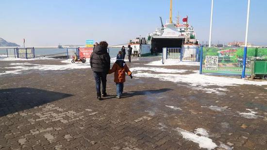 军嫂刘铭俊领着儿子崎崎走向轮渡。记者孙萌 摄