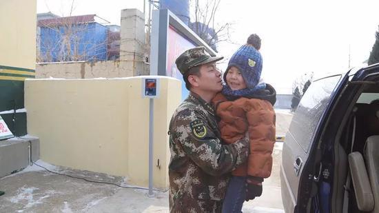 尹丰刚抱着儿子。记者孙萌摄
