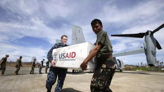 """▲菲律宾和美国军人携手把美国救灾物资卸下美国""""鱼鹰""""军机。"""
