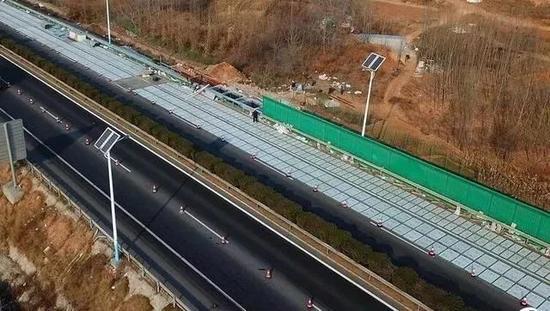 图为11月30日上午,济南南绕城高速上施工职员正在铺设光伏路面