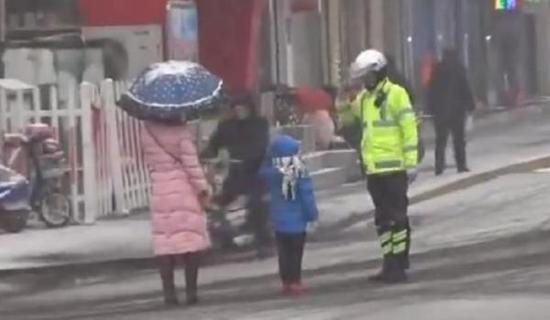 山东邹城交警雪中护幼童,两人互相敬礼道别。@公安部交通安全微发布 图