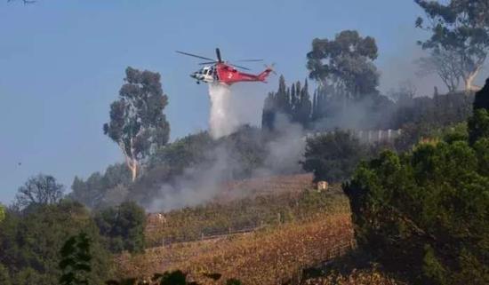 ▲直升飞机正在向莫瑞加庄园洒水灭火 图据美联社