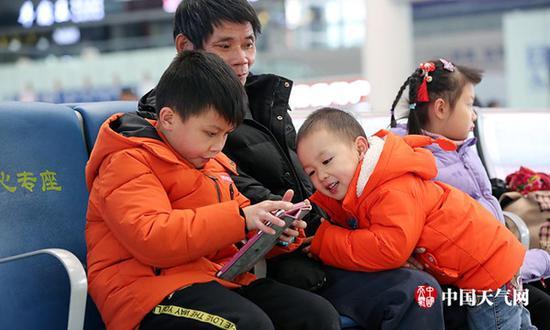 近日,广西南宁气温低迷,候车厅里大人小孩都穿着厚实棉服。(刘英轶/摄)