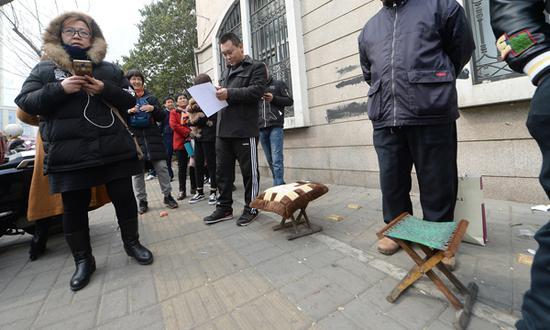 有市民带着小马扎来排队。