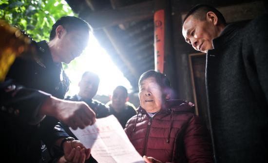 1月21日,在四川泸县方洞镇,民警为艾秀平和儿子杨荣宣读《被拐儿童身份确认通知书》。 新华社记者薛玉斌摄