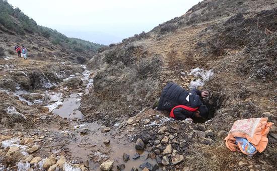 张庭贵伏地饮冰冷的泉水解渴,他说这是他们中途的补水点。上学路上没有带水的习惯,就在这里喝水。