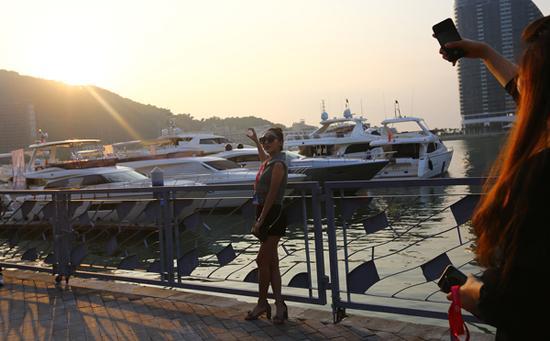2017年12月8日,海南三亚,参观者在展出的游艇旁拍照留念。