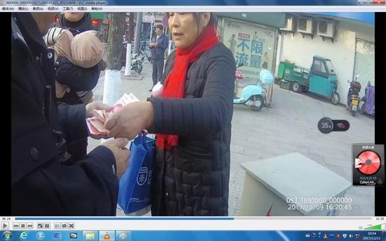△民警接过徐女士捡到的1300元钱,对徐女士拾金不昧的行为表示肯定。