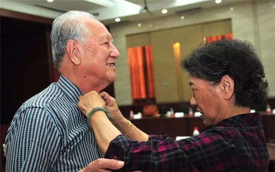 黄旭华夫仁攀李世英(右)在为他收拾着装(2014年5月28日摄)。新华社记者 熊金超 摄