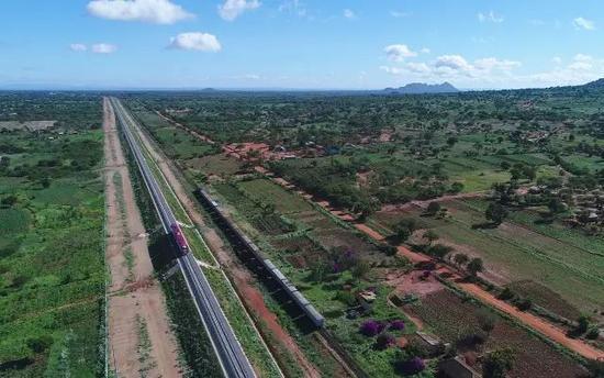 ▲质料图片:正在蒙内(蒙巴萨港-内罗毕)铁路上调试的列车头(左)和百年前设备的米轨铁路上的火车不期而遇。