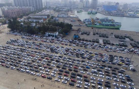 在海口港轮渡码头,准备过海的车辆排队等待登船。