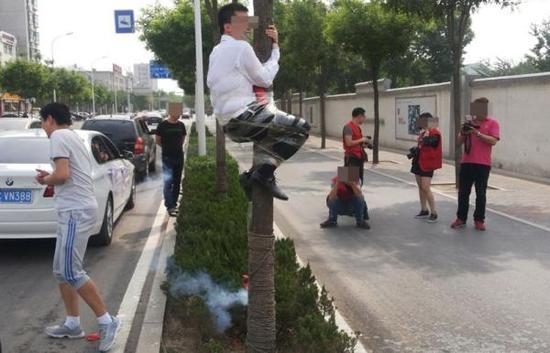 山东淄博,新郎被捆在路边大树上,脸上被涂抹牙膏、屁股上燃放鞭炮、脚上点烟。 视觉中国资料