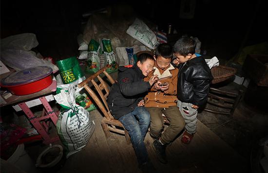 1月20日,湖北恩施宣恩县某村,三名儿童聚集在一起玩游戏。东方IC 资料图
