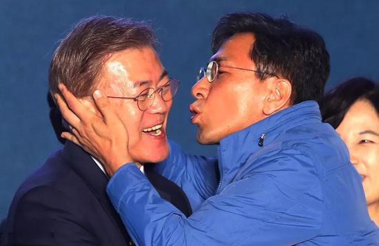 ▲今年年5月9日,韩国首尔,忠清南道知事安熙正亲吻新当选的韩国总统文在寅,祝贺胜利。 图片来源:视觉我国
