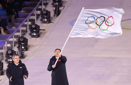 ▲2月25日,北京市市长陈吉宁(右)在闭幕式上挥动奥林匹克会旗。 图/新华社