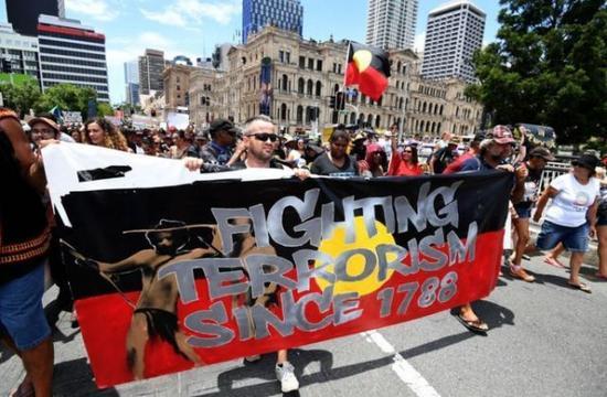 """▲一些游行者甚至打出了""""抗击1788年以来的恐怖主义""""的标语,而背景的旗帜是原住民的旗帜"""