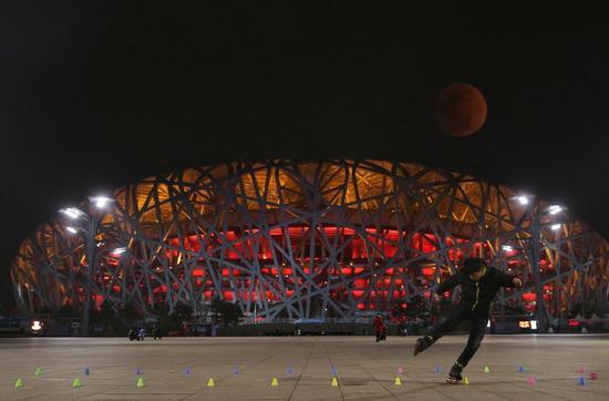 """▲21:20,鸟巢,一位游客在广场溜旱冰,一轮""""血月""""挂在半空。(图为二次曝光) 图/新京报网"""