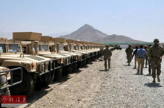 资料图:驻阿美军士兵在检查弃置的悍马车。