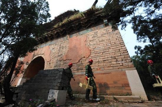 资料图:2011年9月,明十三陵最后一座未修缮陵寝――裕陵正式开工修缮。工人从裕陵残破的明楼下走过。