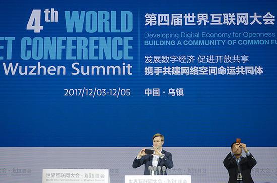 2017年11月30日,浙江嘉兴,第四届世界互联网大会主会场,外籍工作人员站在主席台上拍摄照片。 视觉中国 图