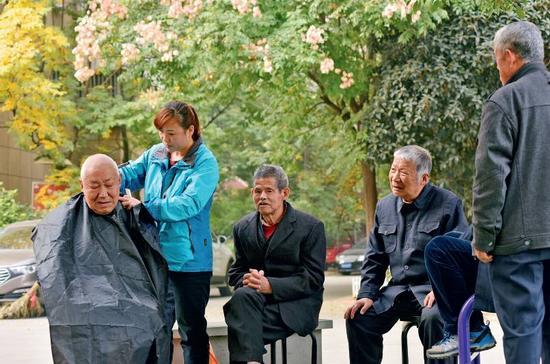 11月9日,在安徽省合肥市蜀山区井岗镇欣塘家园小区广场,47岁的李泽翠在为小区里的老年人免费理发。随着中国人口老龄化的加剧,养老金方面的需求日渐增长。图/视觉中国