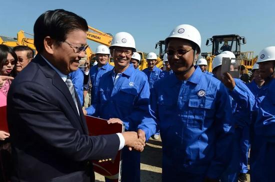 ▲资料图片:在老挝琅勃拉邦,老挝总理通伦(左)在中老铁路开工仪式上与中方员工握手。(新华社)