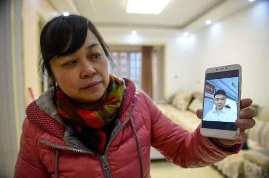 2018年1月4日,重庆。刘金心的照片很少,何小平拿出他仅有的在外打工时自拍给记者看。 视觉中国 图
