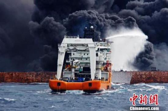 """12日上午10时25分,现场灭火作业第三次启动,画面中""""东海救117""""轮向""""桑吉""""轮喷射泡沫降温灭火。上海海上搜救中心供图"""