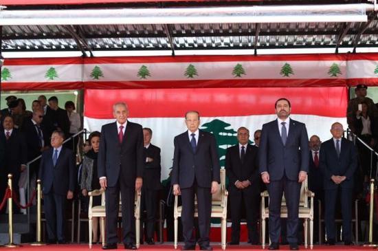 11月22日,在黎巴嫩贝鲁特,黎巴嫩总统奥恩(前排中)、总理哈里里(前排右)和议长贝里(前排左)出席独立日阅兵式。黎巴嫩22日在贝鲁特举行阅兵活动,庆祝结束法国委任统治、实现国家独立74周年。新华社发