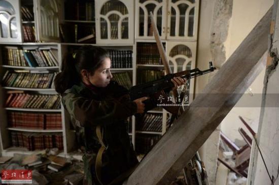 资料图:叙政府军女兵,隐藏在民房中进行警戒。