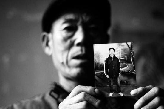 王万保给记者看儿子患病前的照片。