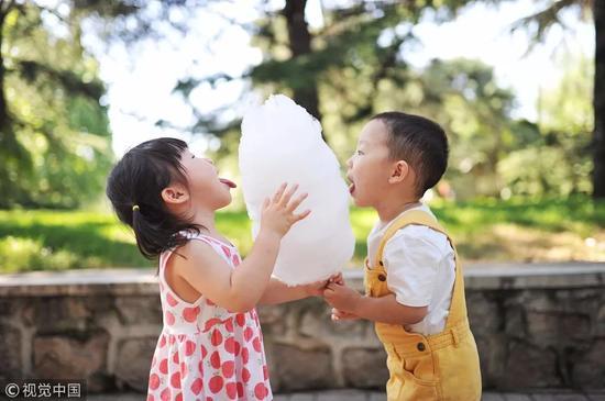 ▲一对兄妹正在公园里一起吃一根棉花糖。图/视觉中国