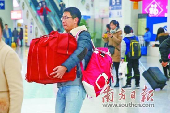 4日,旅客抱着、背着大包小包进站。