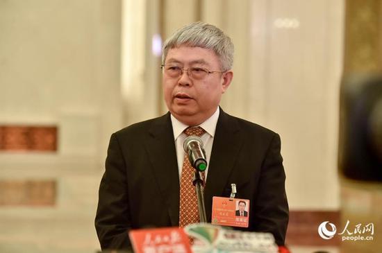 """国务院扶贫办主任刘永富在""""部长通道""""接受采访。(人民网记者 翁奇羽 摄)"""