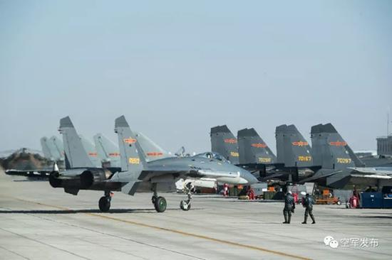 两名飞行员走下战鹰,边走边交流空战体会。
