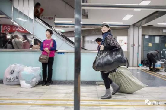 △临近闭市时间,到处都能见到提着、拖着大包小包的人。