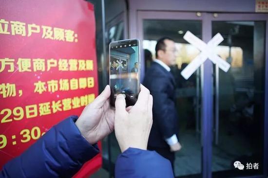 """△ 11月30日,工作人员在大门贴完封条后,""""东鼎""""正式闭市。本文照片新京报记者王子诚 摄"""