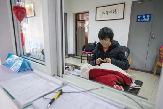 徐根娣在给学生缝补衣服。 记者 陈中秋 摄 (来源:都市快报)