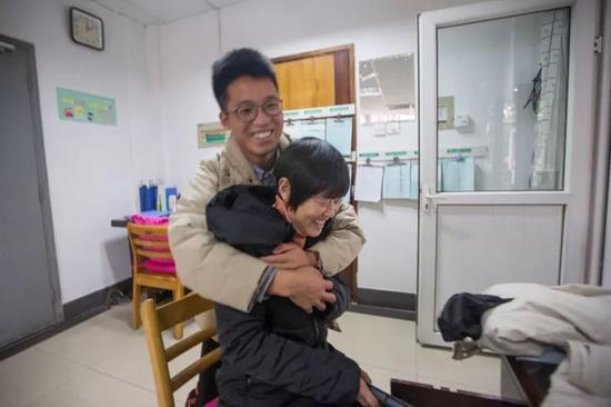 在这栋楼里住了四年的研二学生杨波,听说徐根娣又回来了,特地赶来看望她,一进门就把她抱住。 记者 陈中秋 摄 (来源:都市快报)