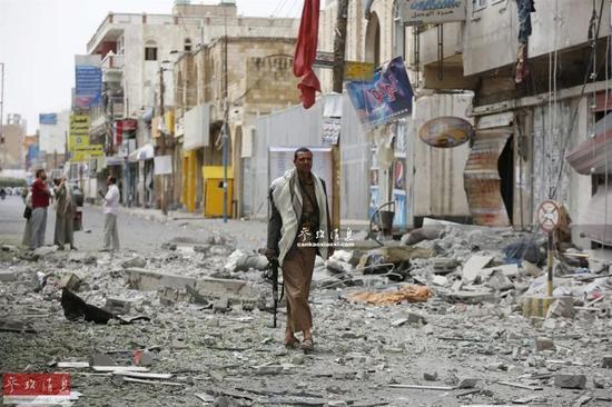 也门首都萨那,一名胡塞武装人员站在已成废墟的建筑物前。