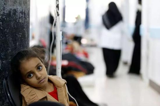 一名感染霍乱的小女孩边打着点滴边睁大双眼看向镜头。