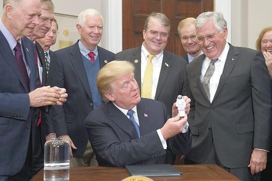 特朗普11日在签署第一份太空政策指令后拿起一个宇航员模型玩具。