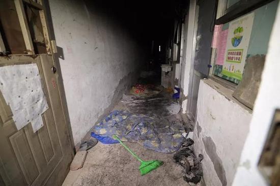 一楼楼道里,地面铺着十床左右被子。