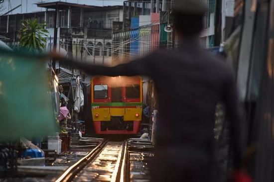 在泰国中部沙没颂堪府的美功市场,一名铁路警察指挥通勤列车进站。新华社记者李芒茫摄
